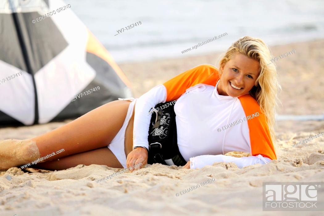 Stock Photo: Smiling young blonde woman lying on the beach.