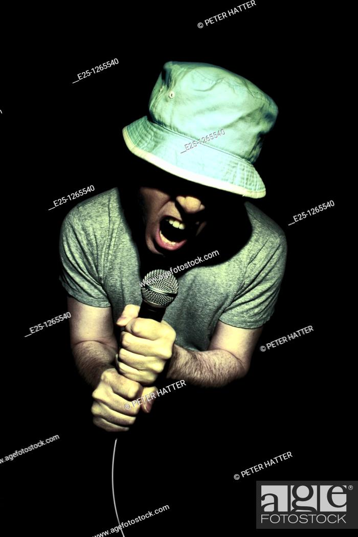 Stock Photo: Adult wearing a hat and gray tee shirt male sings in to microphone. Isolated on black background.
