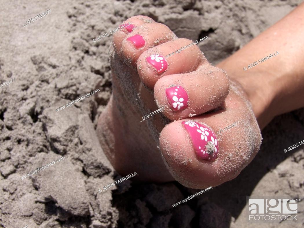 Stock Photo: Pink nails decorated with floral motifs.