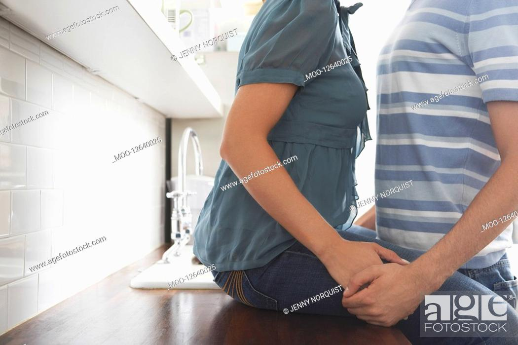 Stock Photo: Couple holding hands in kitchen mid section.