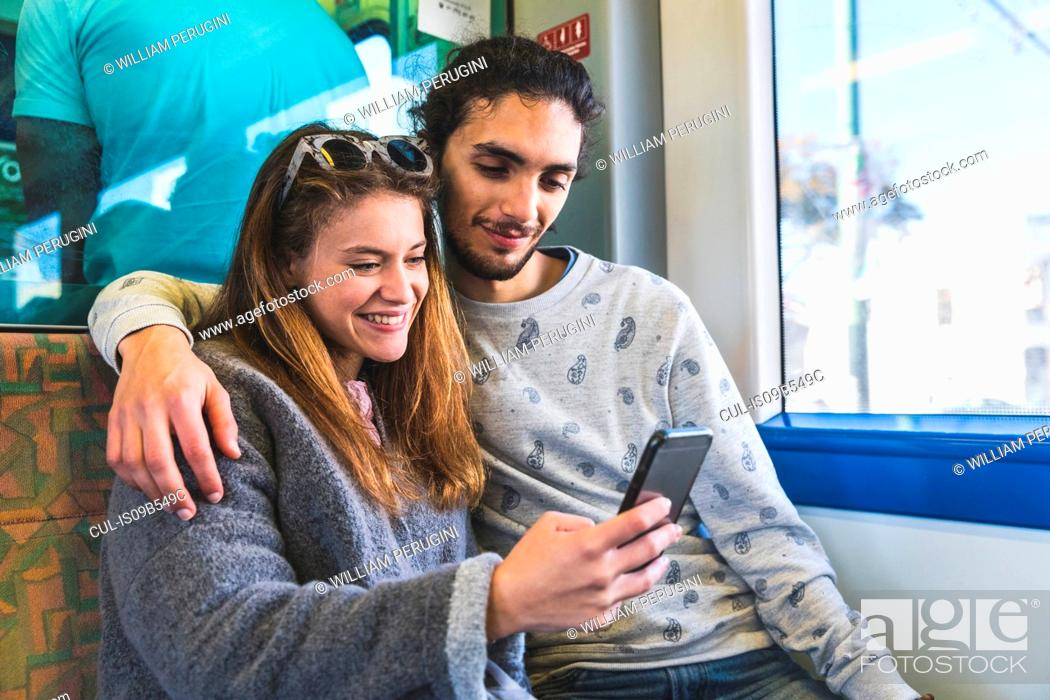 Stock Photo: Young couple, sitting on train, taking selfie with smartphone, Lisbon, Portugal.