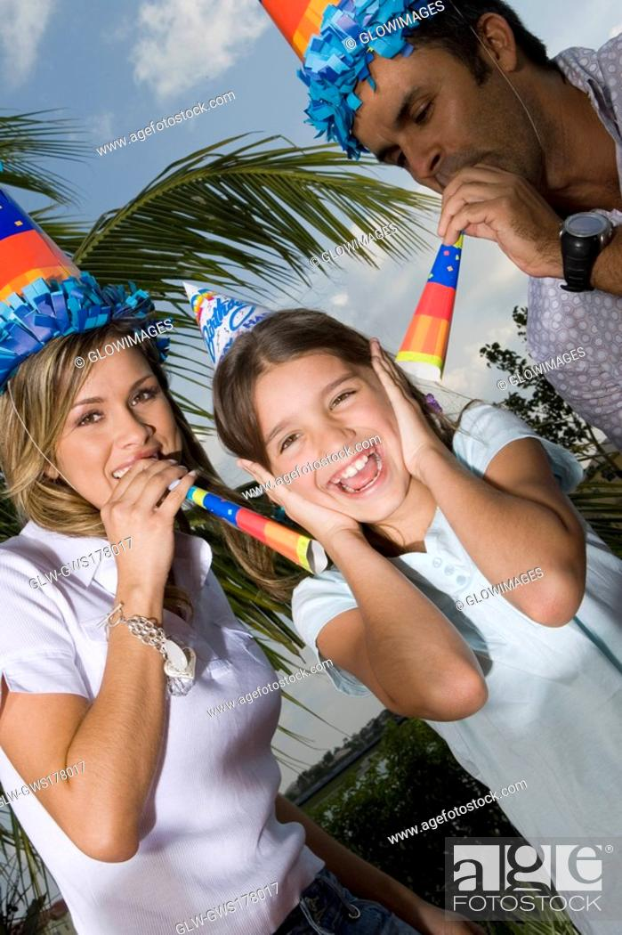 Stock Photo: Portrait of a girl laughing with her parents blowing party horn blowers.