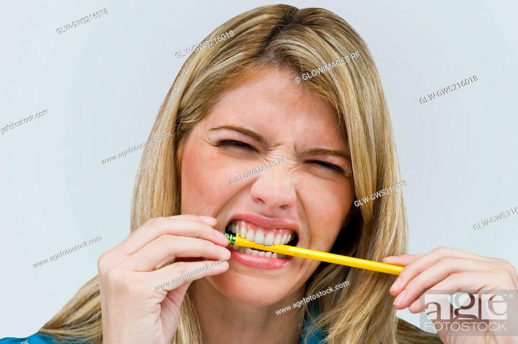 Stock Photo: Close-up of a young woman biting a pencil.
