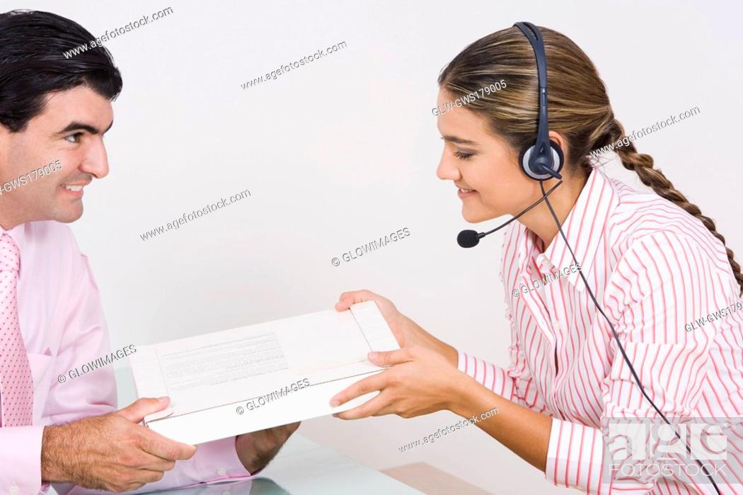 Stock Photo: Side profile of a receptionist wearing a headset and receiving a box from a businessman.