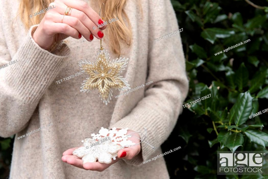 Stock Photo: Hands of woman holding Christmas decorations.