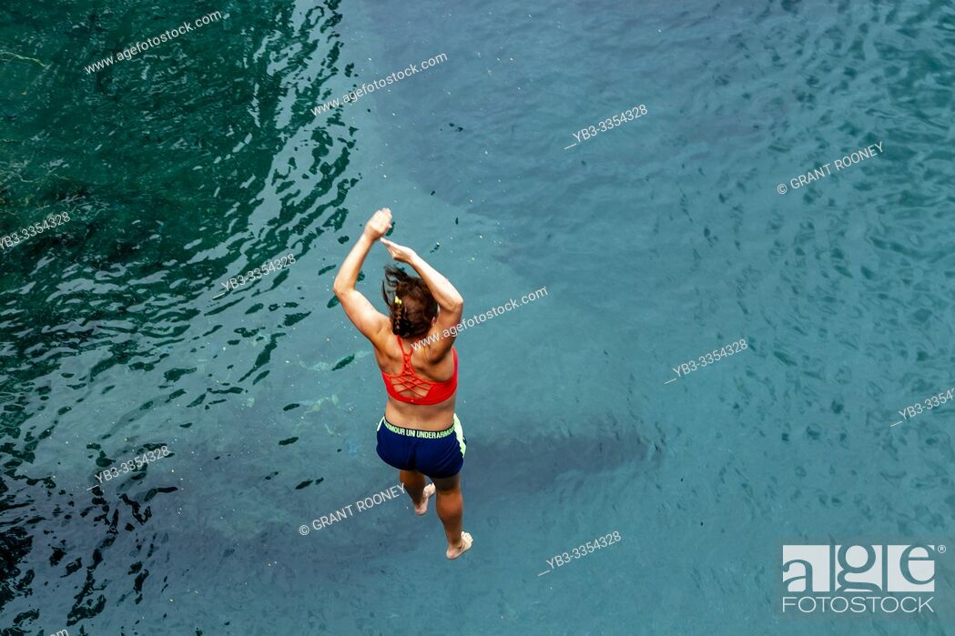 Stock Photo: A Young Woman Jumps Into The Blue Pools (near Makarora), Mt Aspiring National Park, South Island, New Zealand.