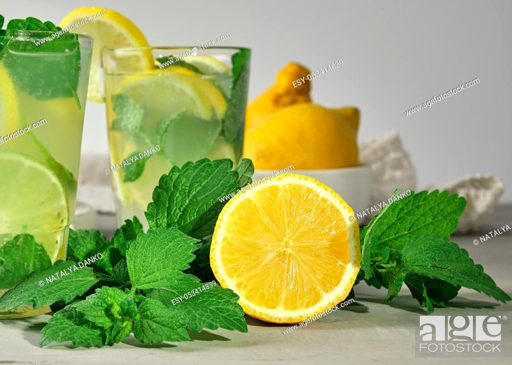 Stock Photo: half a yellow lemon and fresh green mint, next to two glasses with a summer refreshing drink.
