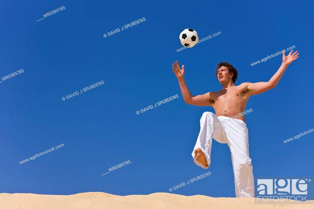 Stock Photo: Beach Soccer player keeps eye on ball.