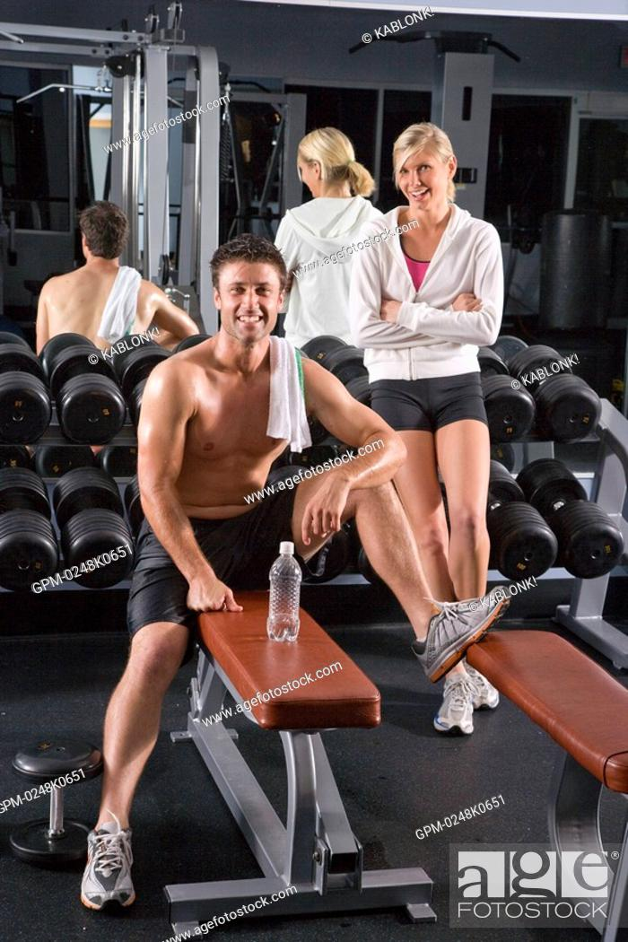 Portrait Of Young Woman Standing By Dumbbells And Young Man