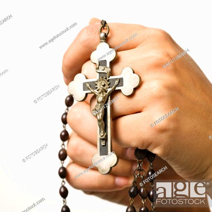Stock Photo: Woman's hands holding rosary with crucifix.