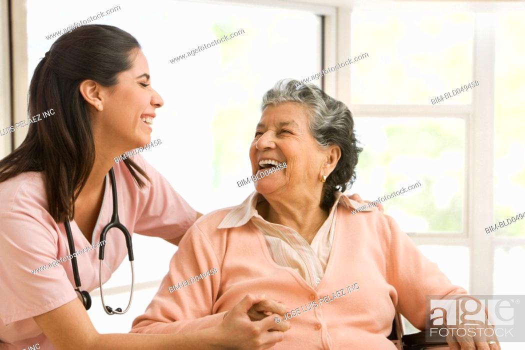 Stock Photo: Senior Hispanic woman and nurse laughing.