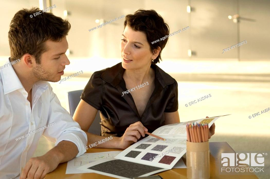 Stock Photo: Two interior designers discussing on a color swatch.