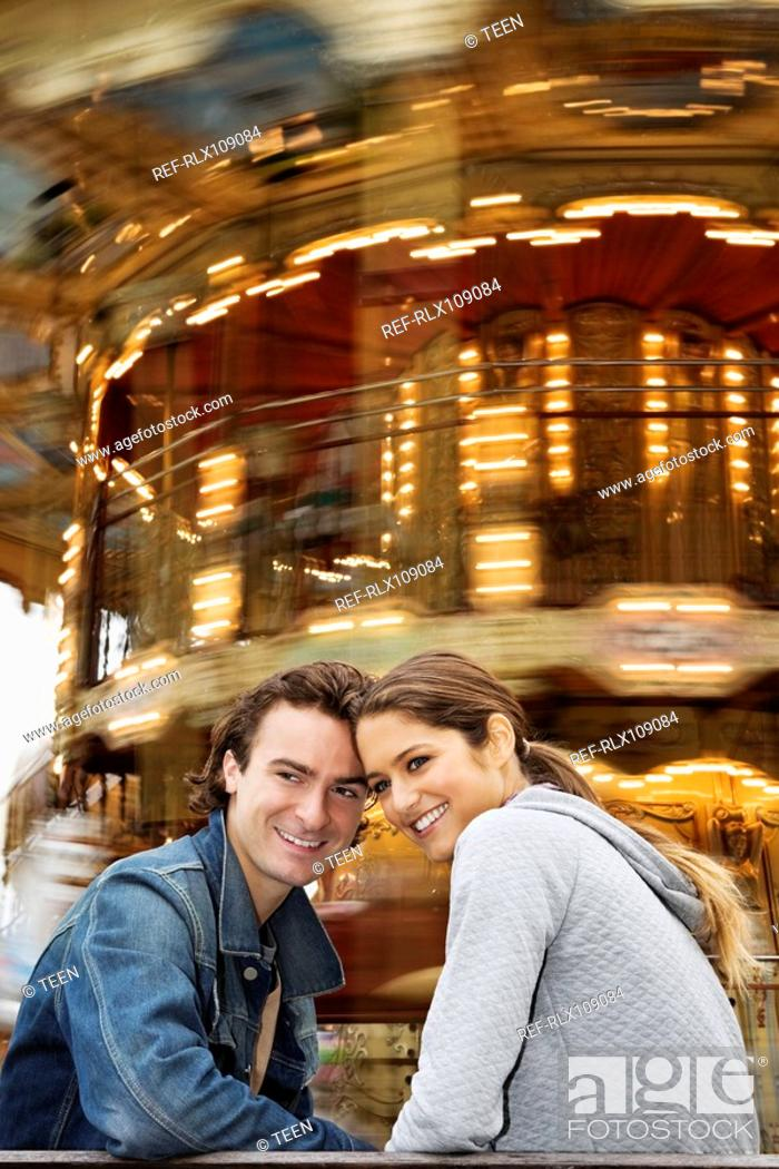 Stock Photo: Young couple sitting on bench with Carousel in background, Paris, France.