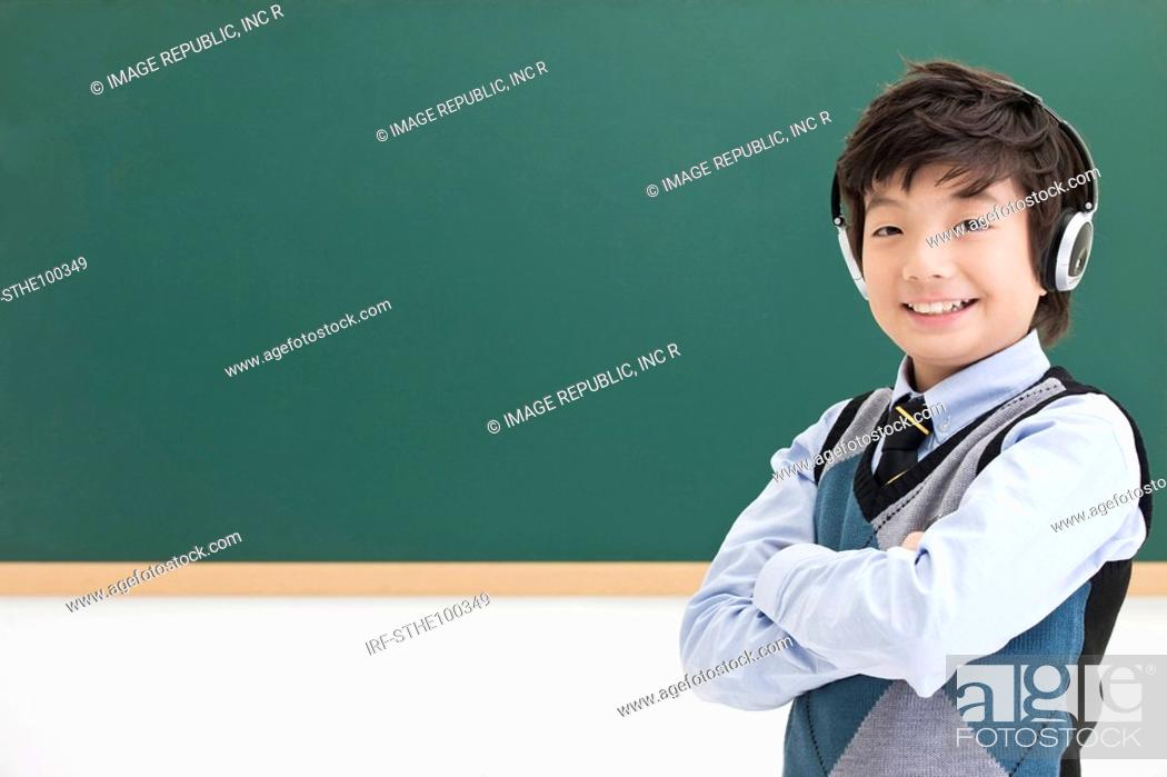 Stock Photo: boy in front of blackboard.