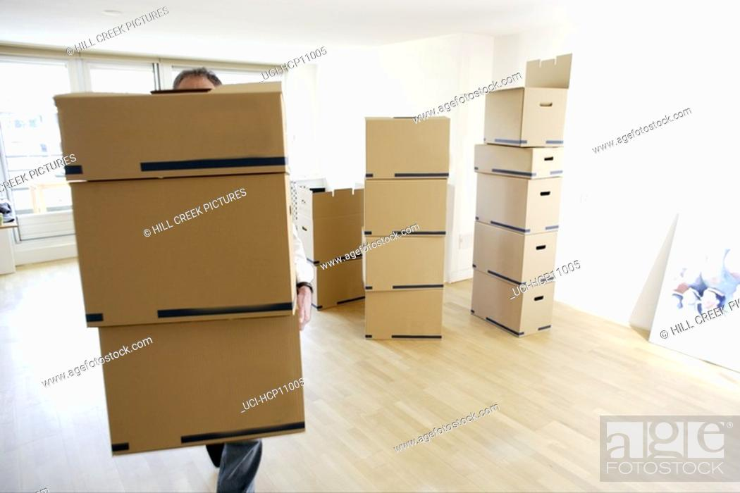 Stock Photo: Man carrying stacked boxes.
