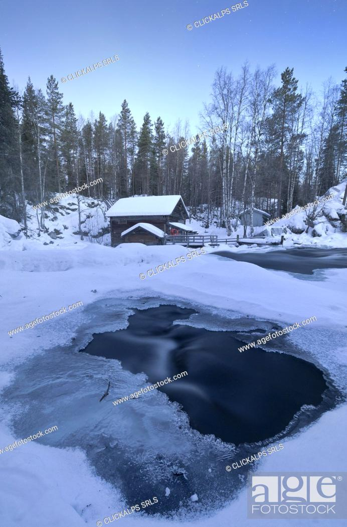 Stock Photo: The dusk frames the frozen water in the snowy woods and the wooden hut Juuma Myllykoski Lapland region Finland Europe.
