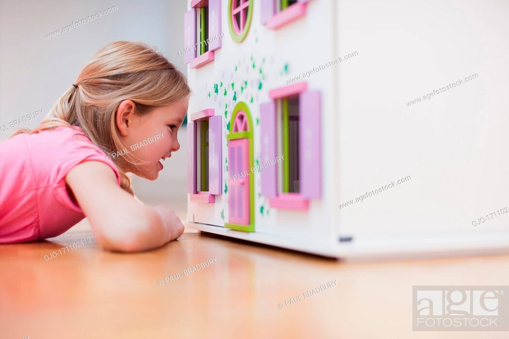 Stock Photo: Girl peering into dollhouse.