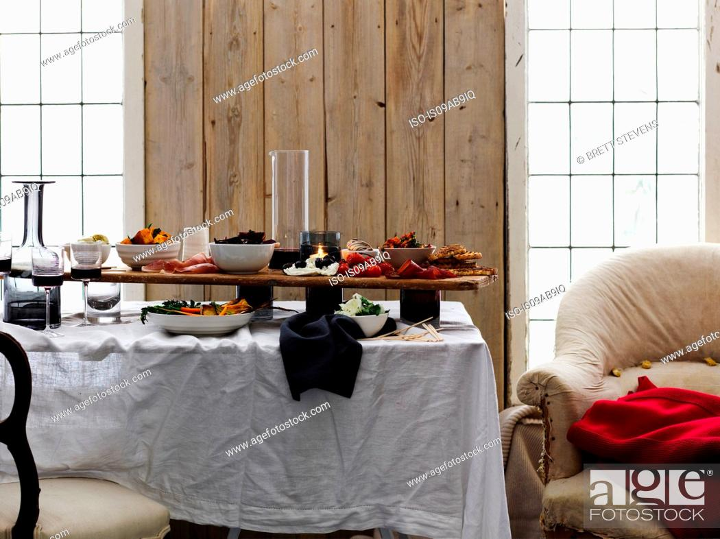 Stock Photo: Dining room with selection of antipasto on table.