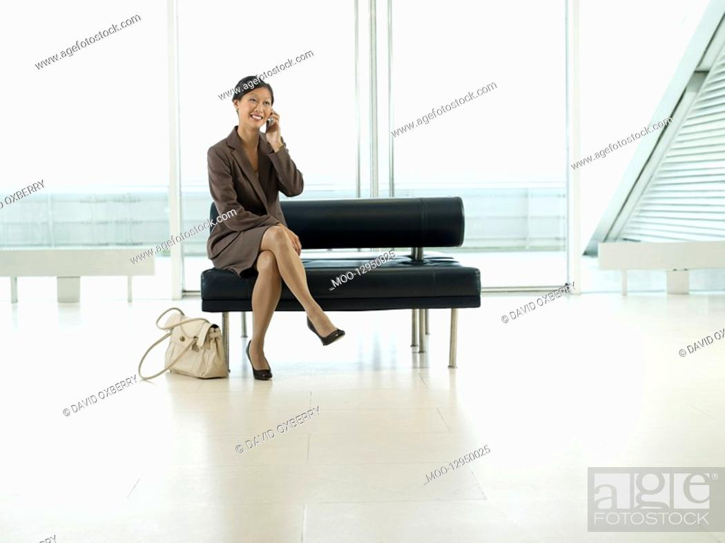 Stock Photo: Businesswoman Sitting on Bench in airport talking on mobile.