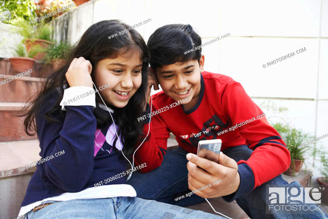 Stock Photo: Close-up of a brother and his sister listening to an MP3 player.