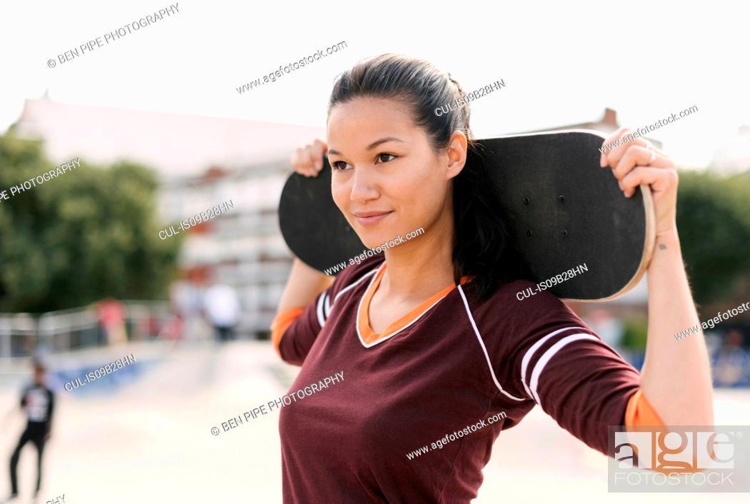 Photo de stock: Portrait of female skateboarder carrying skateboard on shoulders.