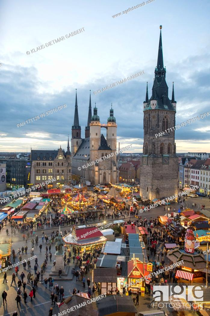 Stock Photo: Visitors walk across the christmas market in Halle an der Saale, Germany, 28 November 2017. The christmas market opened in the late afternoon and runs until 23.