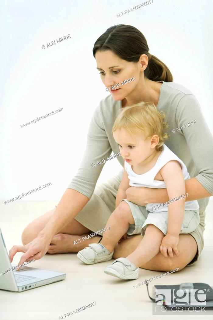 Stock Photo: Professional woman sitting on the ground, using laptop, holding toddler on lap.