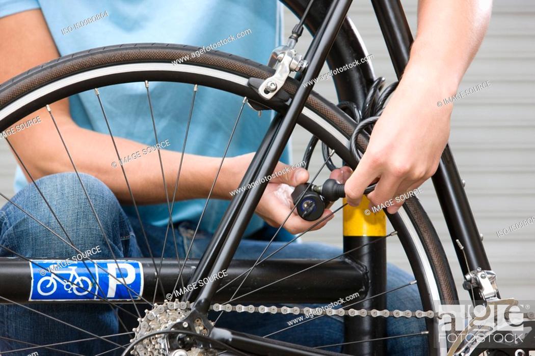 Stock Photo: Man locking bicycle.