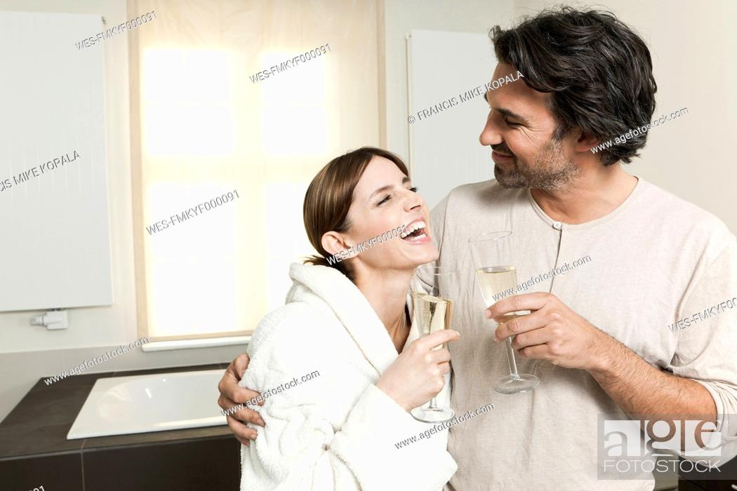 Stock Photo: Germany, Berlin, Mature couple in bathroom with sparkling wine.