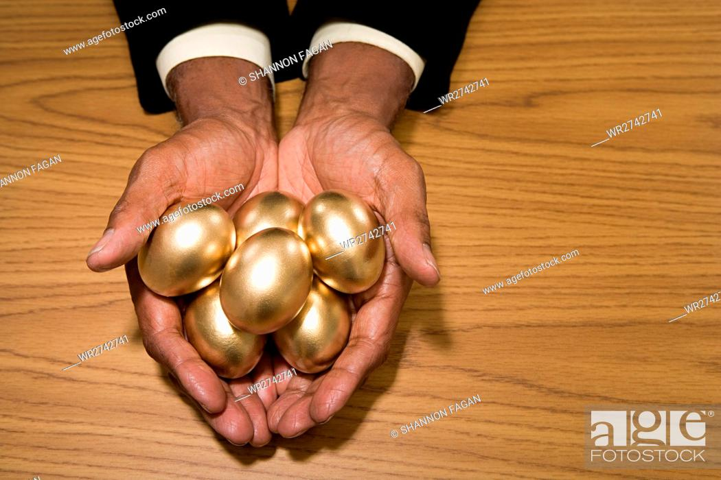 Stock Photo: Man holding golden eggs.