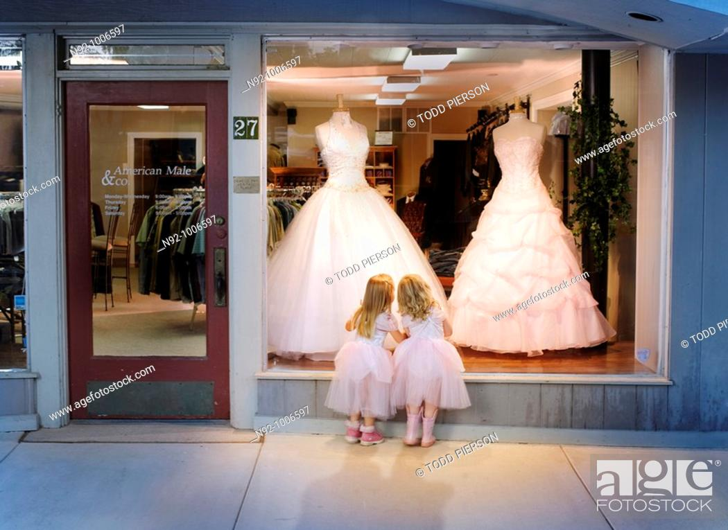 Stock Photo: 2 girls standing at window looking at gowns dreaming about a dance.