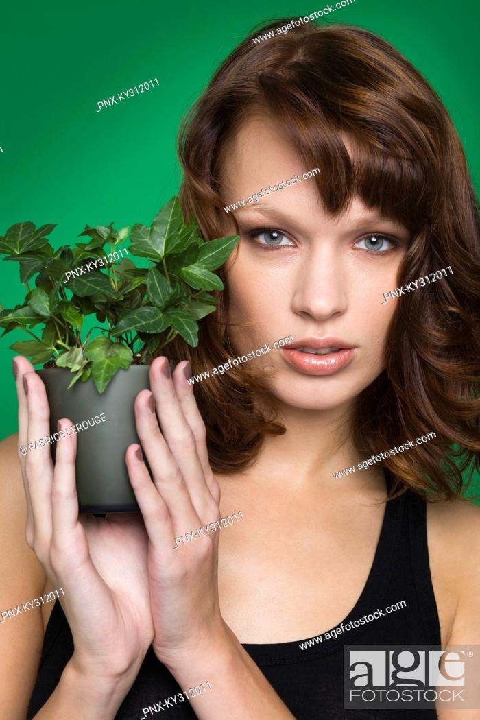 Stock Photo: Young woman holding pot of ivy.