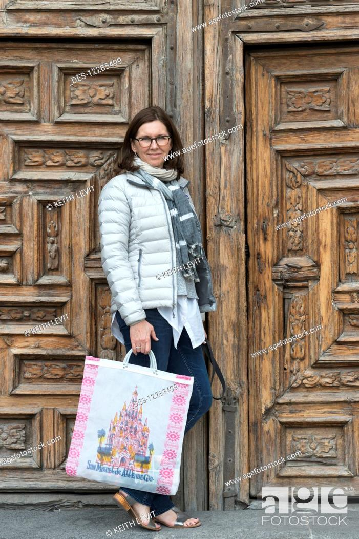 Imagen: A woman standing with a shopping bag outside ornate wooden doors; San Miguel de Allende, Guanajuato, Mexico.