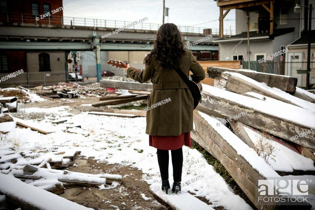 Stock Photo: Rear view of young woman on snowy city wasteland playing guitar.