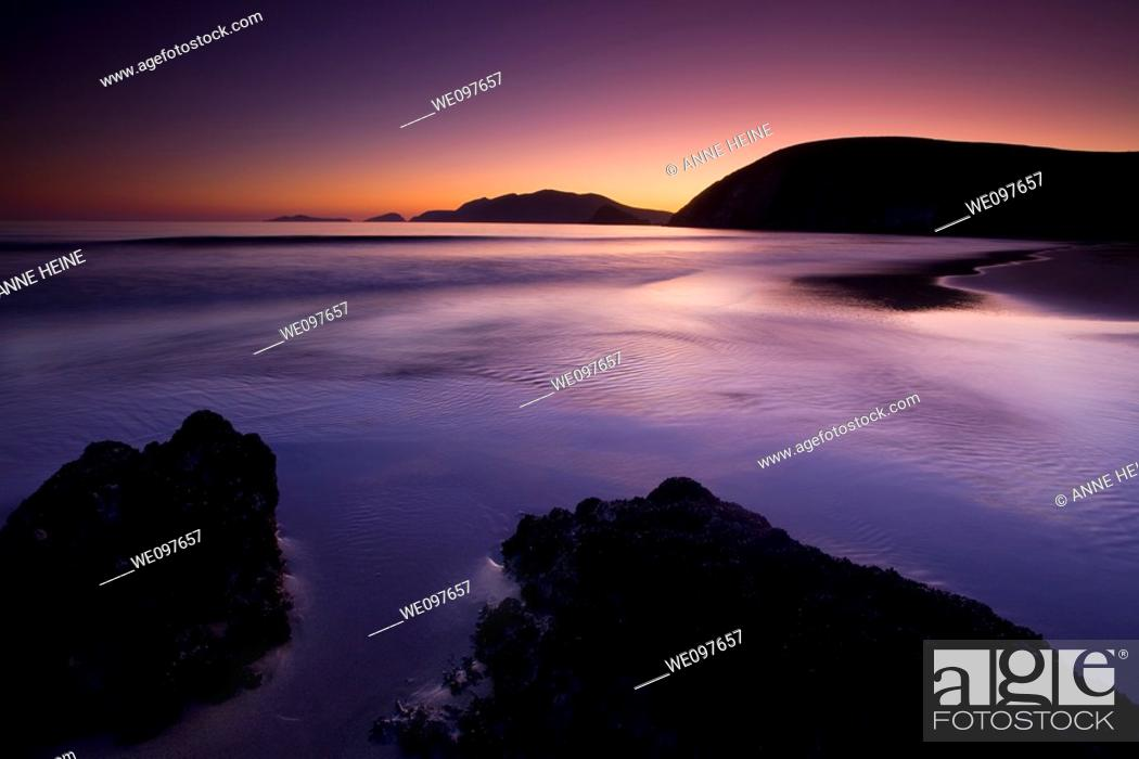 Stock Photo: beach at twilight with rocks in foreground, cliffs in background, dark.