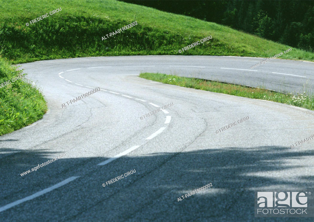Stock Photo: Hairpin turn through grassy landscape.