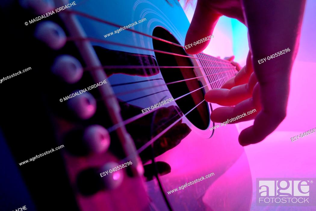Stock Photo: Closeup of an acoustic guitar played by a girl.