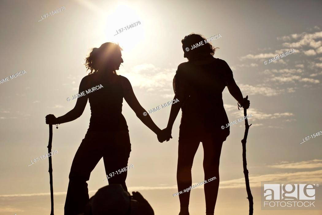 Stock Photo: Silhouette of two girls holding hands at sunset, finisterre.
