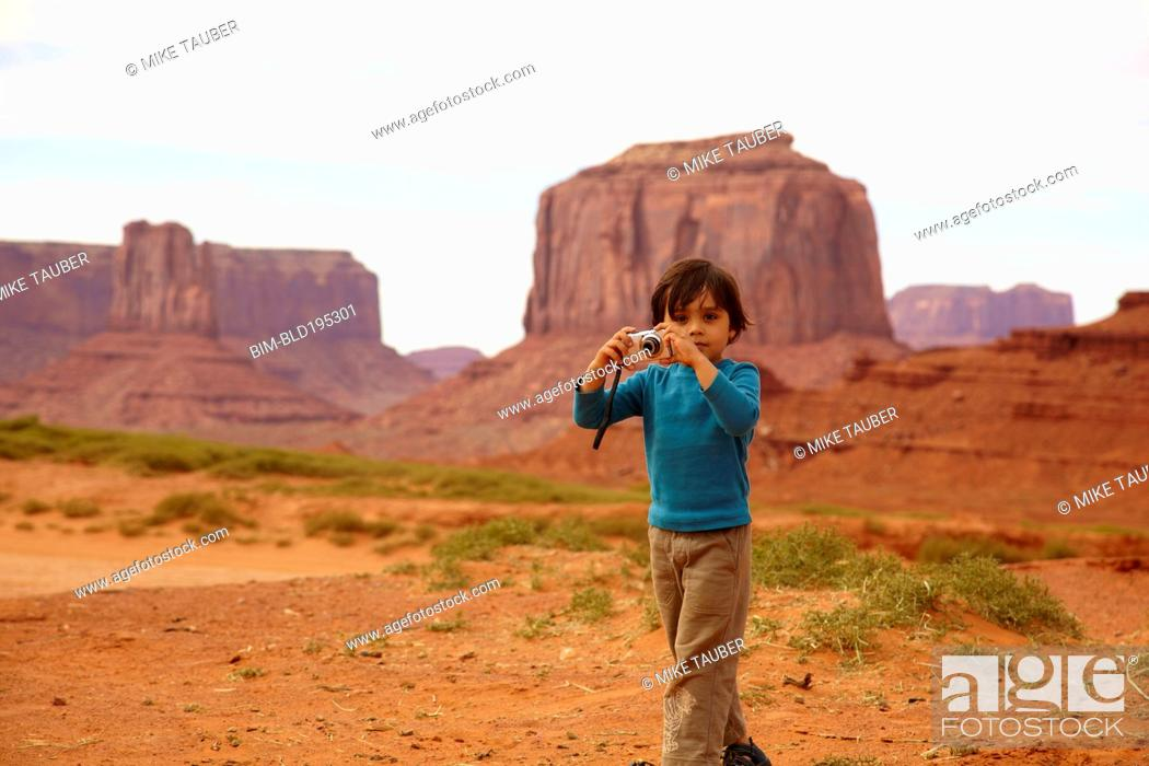Stock Photo: Mixed race boy taking pictures in Monument Valley.