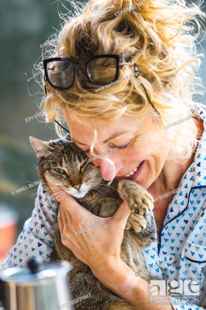Photo de stock: Blonde young mature woman with glasses in pyjamas at home in breakfast time, reading a magazine and having a moment with his cat.