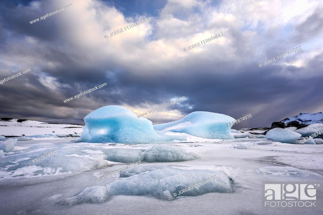 Stock Photo: Big piece of blue ice trapped on the ice of the Fjallsarlon glacial lagoon in winter.