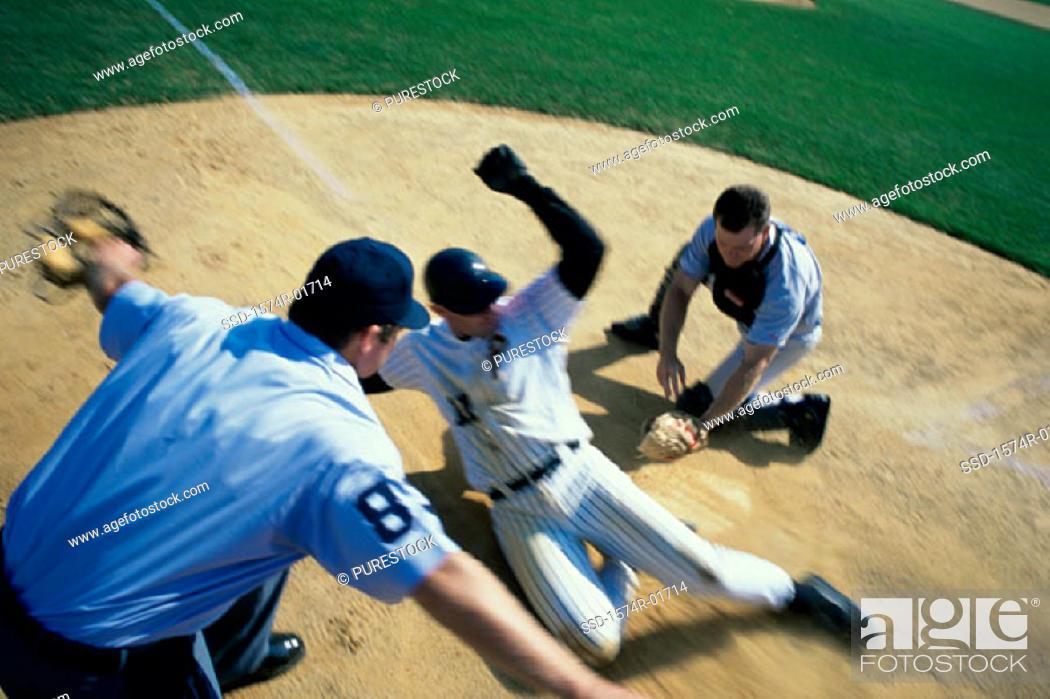 Stock Photo: Baseball player sliding into home base.