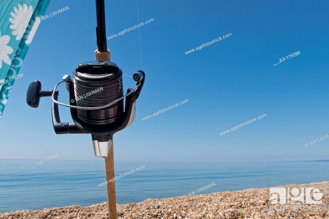 Imagen: Close-up of fishing reel and rod on pebble beach with ocean and blue sky background.