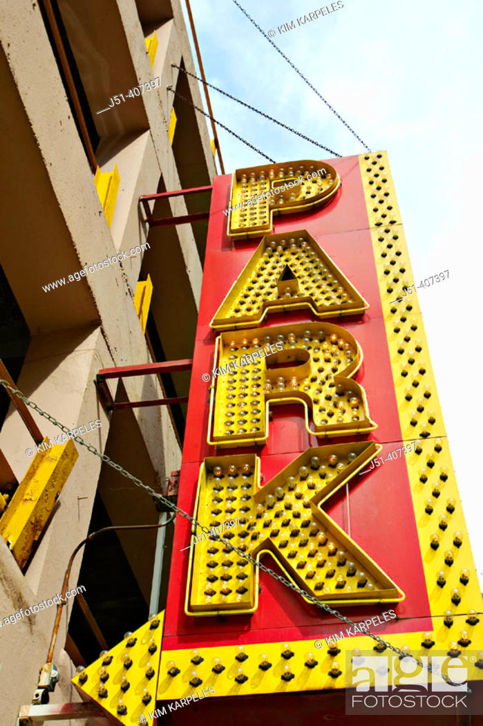 Stock Photo: USA, Illinois, Chicago. Yellow parking sign with arrow point to garage, many lightbulbs.