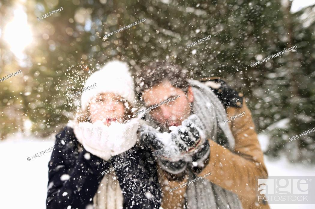 Stock Photo: Young couple blowing snow.