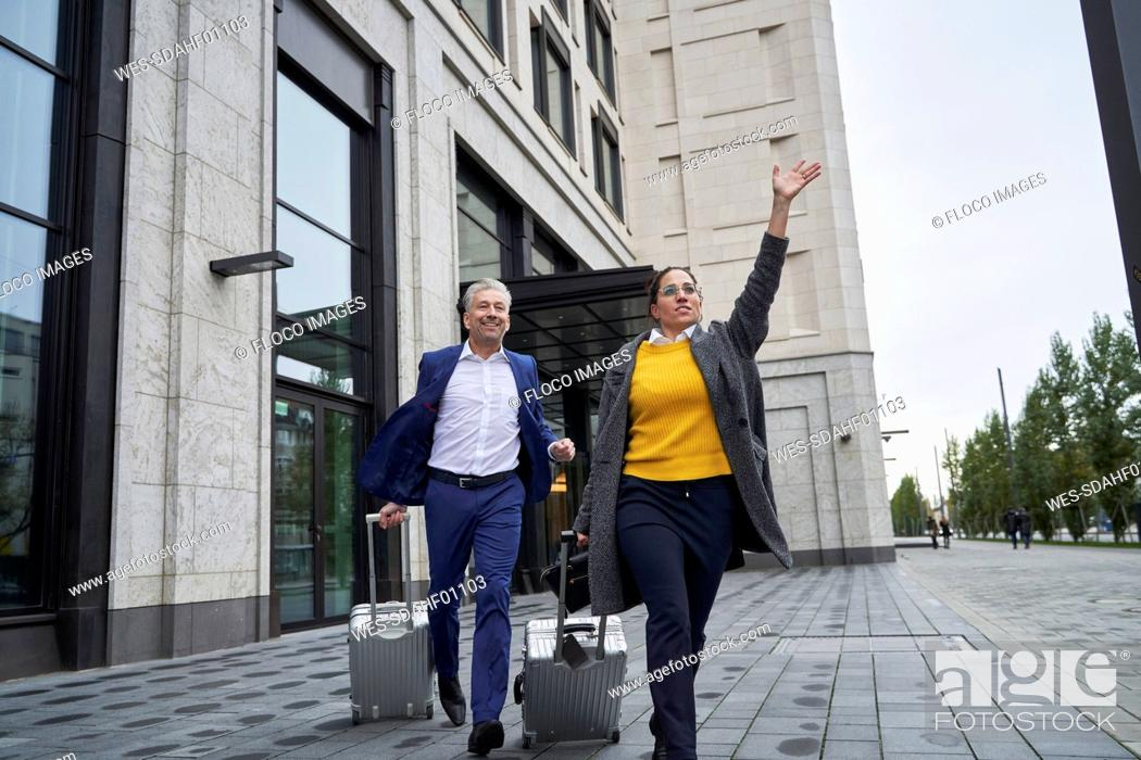 Stock Photo: Business colleagues running with wheeled luggage on footpath while waving in city.