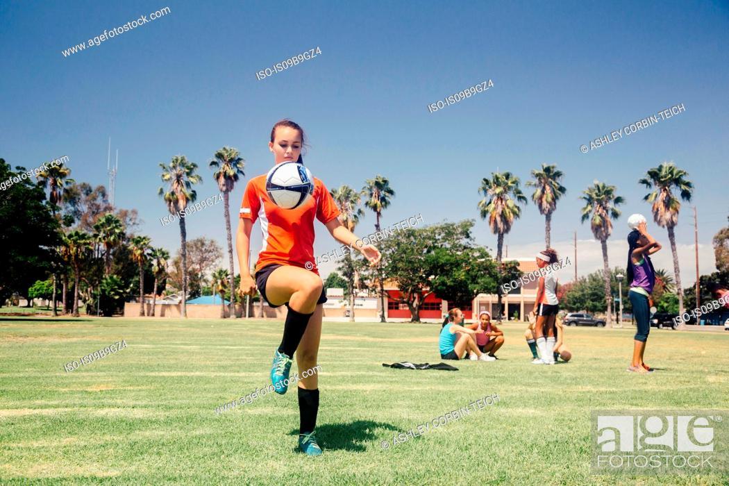 Imagen: Teenage schoolgirl soccer player practicing keepy uppy on school sports field.