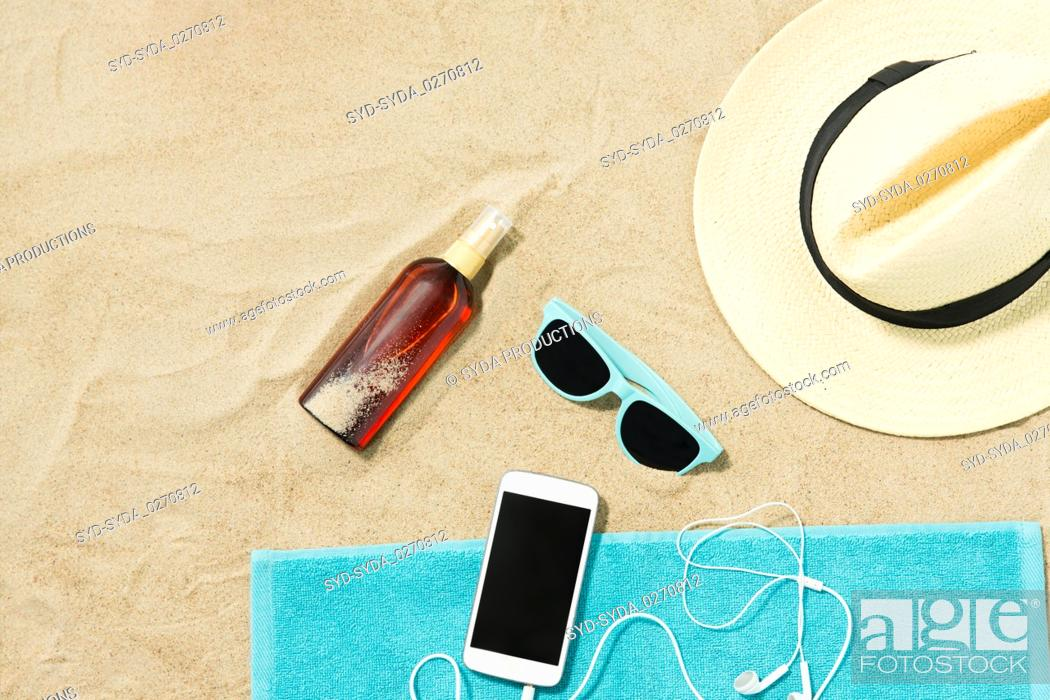 Stock Photo: smartphone, hat, flip flops and shades on beach.