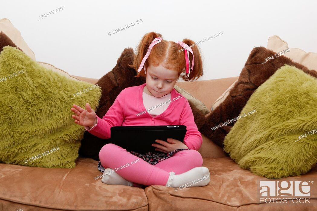 Stock Photo: Little girl on a computer tablet, sat on sofa.