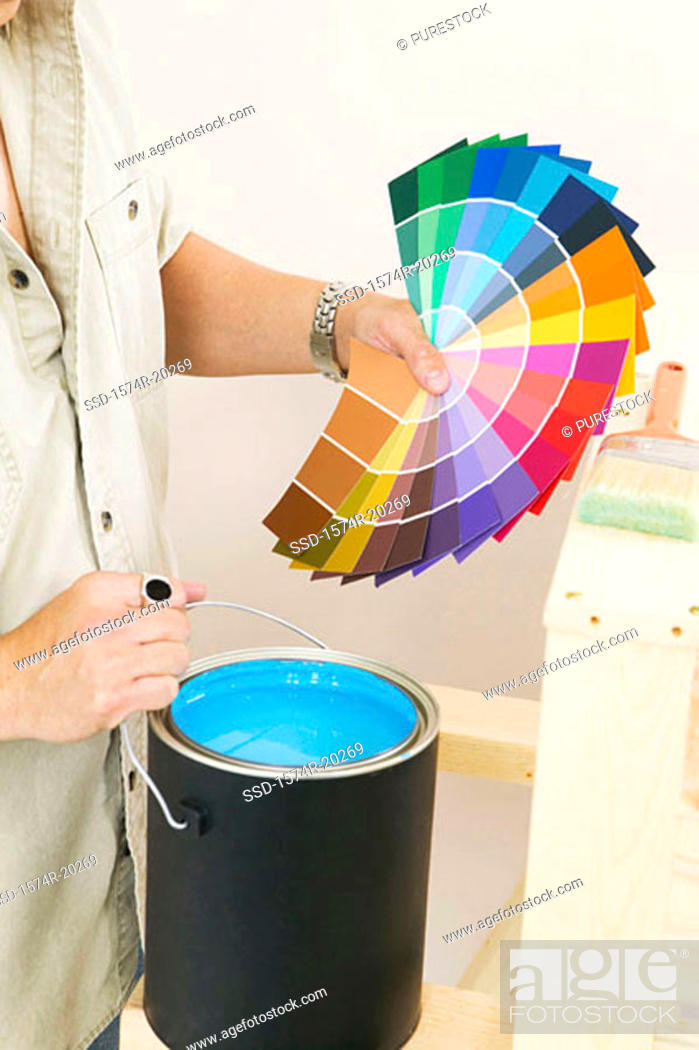 Stock Photo: Mid section view of a man holding color swatches and a paint can.